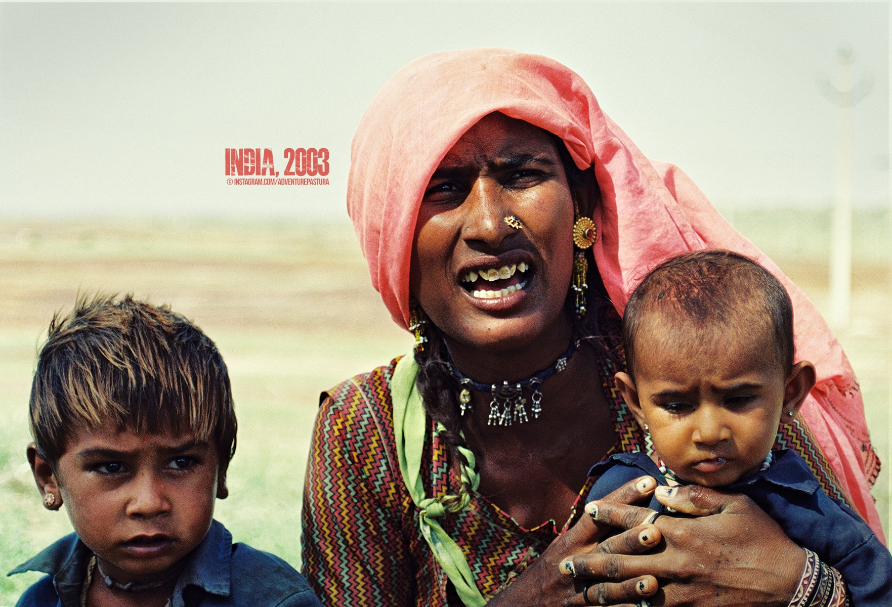 A poor Indian mother begs for help with her two kids in Rajastan, India. Photo by © Piero Zilio.