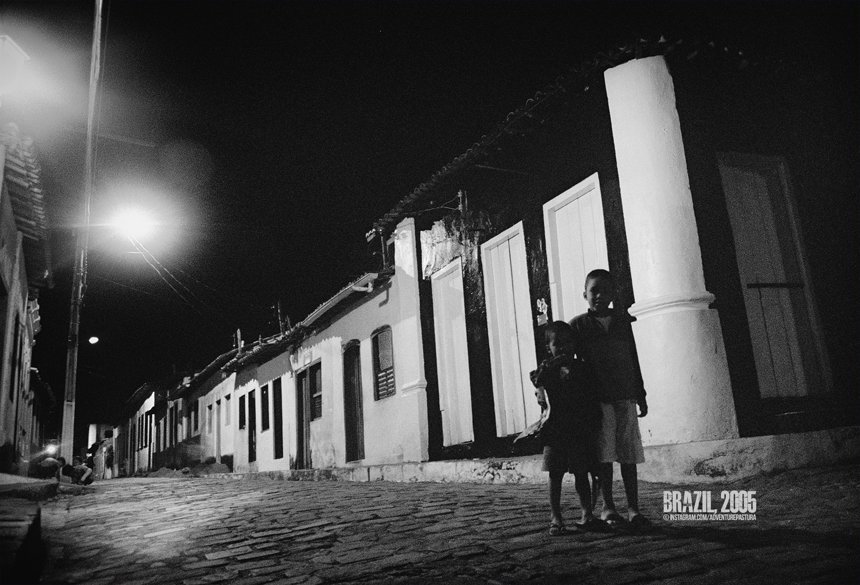 Two curious kids hide on the dark side of the alley somewhere in the Chapada Diamantina, Brazil. Photo by © Piero Zilio.